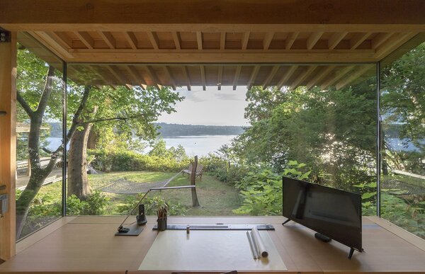 This enchanting cabin features an expansive 10-foot-wide insulated panel of glass which frames a panoramic view of the water from the workstation. The desk and cabinets are by Korben Mathis Woodworking; the desk lamp is from TaoTronics.