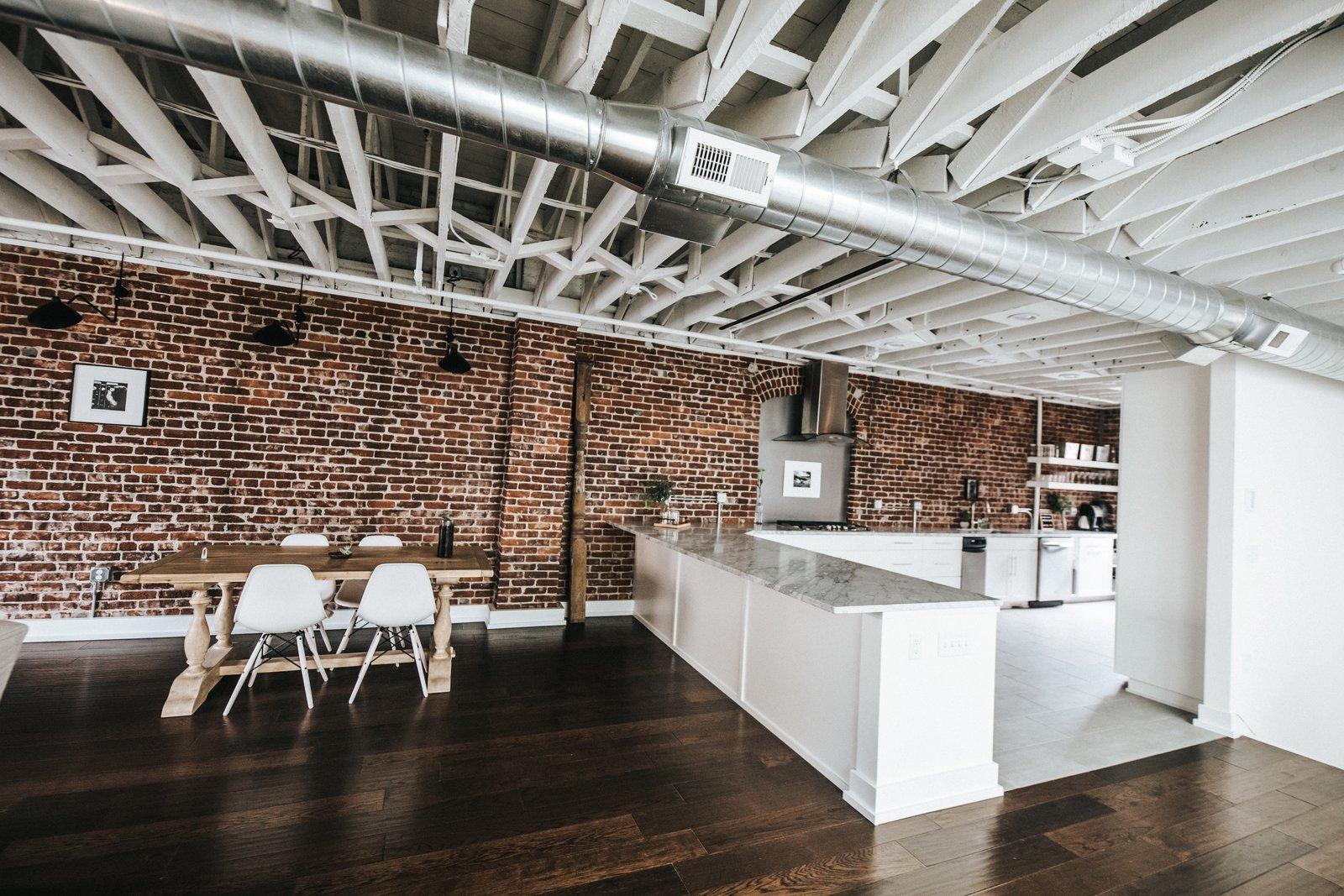 Kitchen, Dark Hardwood Floor, Terrazzo Floor, Dishwasher, White Cabinet, Cooktops, Range Hood, Brick Backsplashe, Marble Counter, and Wood Cabinet Kitchen/Dining View  Frindle