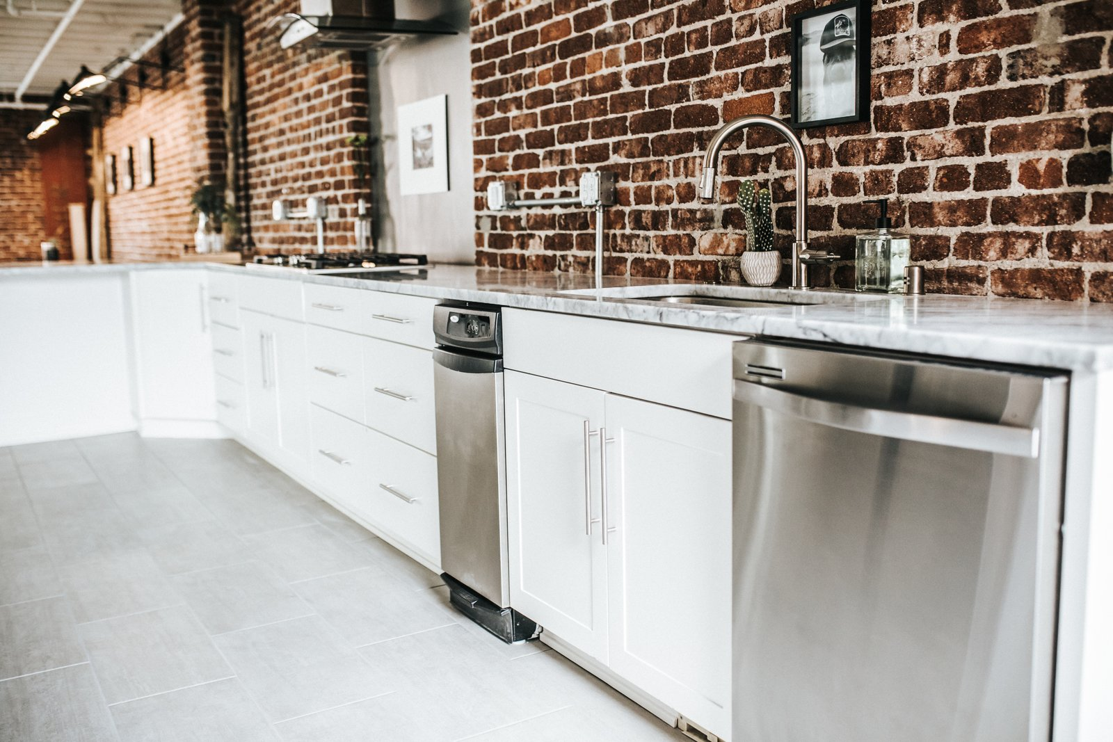 Kitchen, Terrazzo Floor, Wood Cabinet, Cooktops, Range Hood, White Cabinet, Brick Backsplashe, Marble Counter, and Dishwasher Kitchen  Frindle