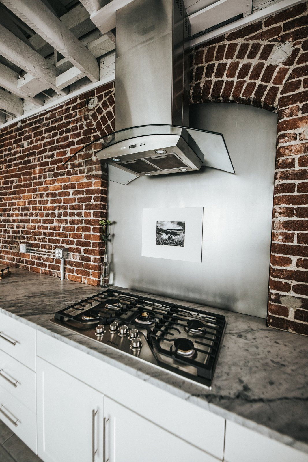 Kitchen, Brick Backsplashe, Marble Counter, Terrazzo Floor, Range Hood, White Cabinet, Cooktops, and Wood Cabinet Cooktop  Frindle