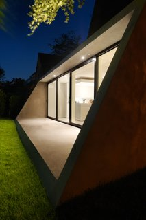The concrete extension continues the dramatically sloped roofline of the original structure.