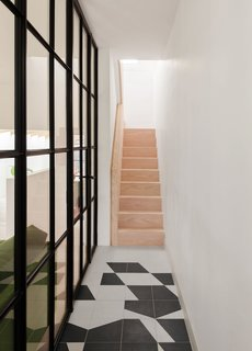 The entrance hallway features tiles from the Puzzle collection by Barber Osgerby for Mutina. The original staircase has been over-clad with Douglas fir timber that matches the timber used in the new flooring on the ground floor.