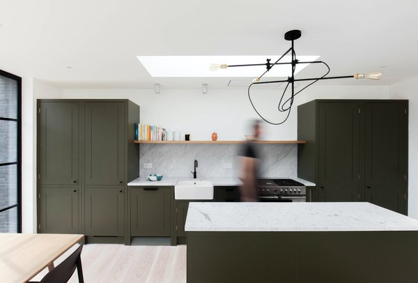 The kitchen features timber cabinetry in the same olive green colour as the front door and the walls in the master bedroom.