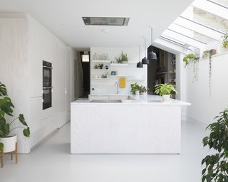 The kitchen features whitewashed Douglas fir joinery with an enamel splatterware worktop by Vlaze on a seamless resin floor by Puur. Plants bring a relaxed feeling to the interior.