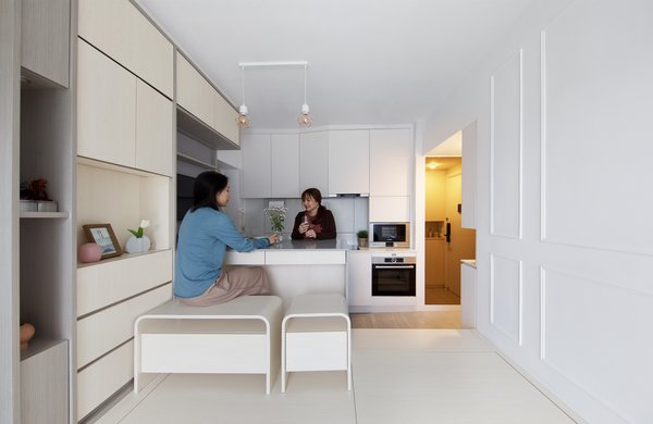 The open-plan kitchen is adjacent to the living space and features clever storage solutions throughout, including in the bespoke timber bench seats.