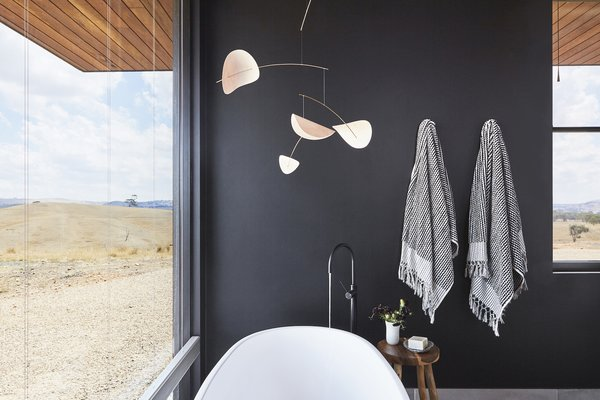 The bathtub has sweeping views over the surrounding landscape, yet it's still private thanks to the remote location. The black wall emphasizes the feeling of refuge.