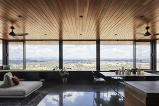In the living room, wall-to-wall windows frame views of the landscape to the east.