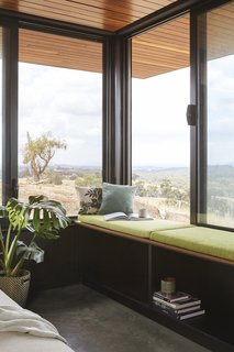 A cushioned window seat with storage beneath it runs the entire length of the living room.