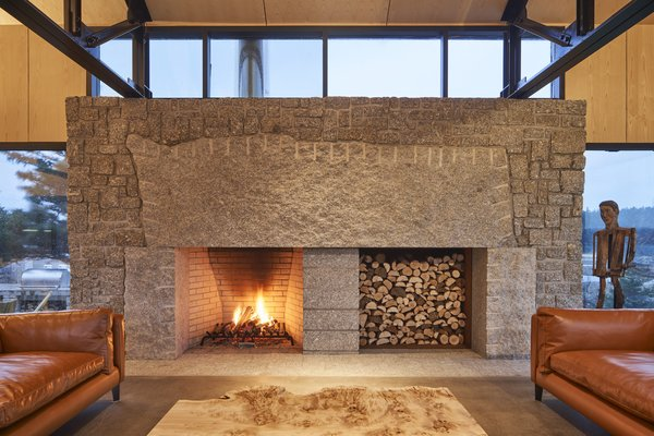 The 16-foot fireplace is crafted from local granite and features a five-ton, live-edge mantle stone that carries the marks of its making.