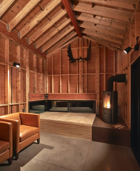 The rustic shed functions as a retreat for the client's children and features a stage-like plinth as the hearth.