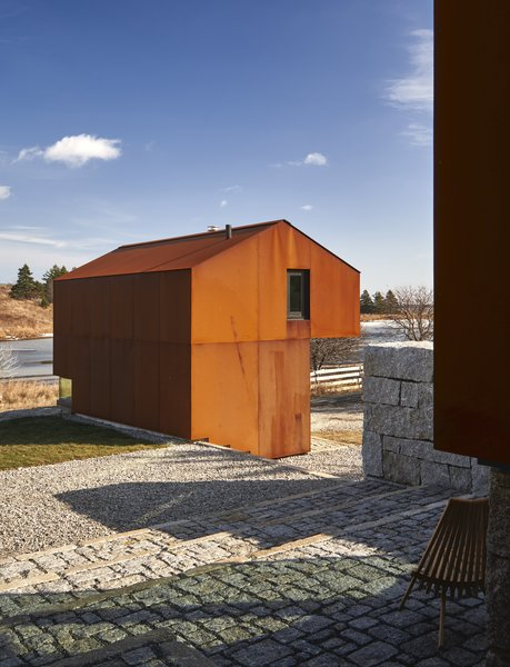 The Cor-Ten shed structure is used as a retreat by the clients' children. It sits on the roadside granite retaining wall, and a low corner window offers views back to the Shobac Campus.