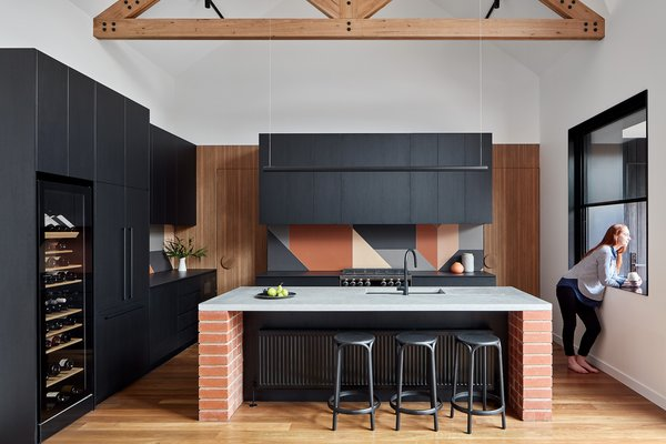 A red brick and concrete island acts as a centerpiece in the kitchen. The benches to the rear and side of island are made from Dekton Sirius reconstituted stone and are surrounded by black laminate cabinetry. The tiles used for the backsplash are Tierras by Patricia Urquiola for Mutina.