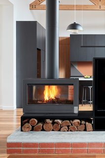 The two-way fireplace that divides the living space sits on a red brick and concrete plinth, echoing the use of materials in the kitchen island. The lighting in the living area is from NAU and Oty Light.