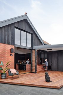 The external brick walls are part of the 1990 addition. The upper part had been rendered in acrylic and painted butter yellow. This was removed and the section was re-clad with a charred solid timber shiplap cladding. An enormous double-height window floods the living space with natural light.