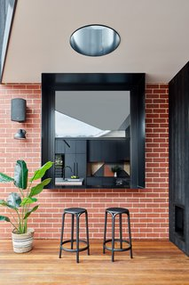 A black-framed servery window connects the kitchen to the covered deck, enabling a relaxed indoor/outdoor style of living.