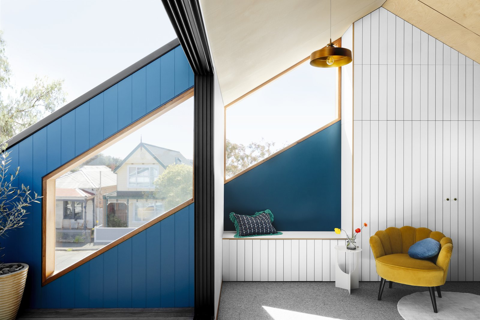 All of the northern windows follow the angle of the existing roofline and align with each other between the living room, deck, and stairwell. Full-height glass sliding doors open directly from the living room onto the deck.