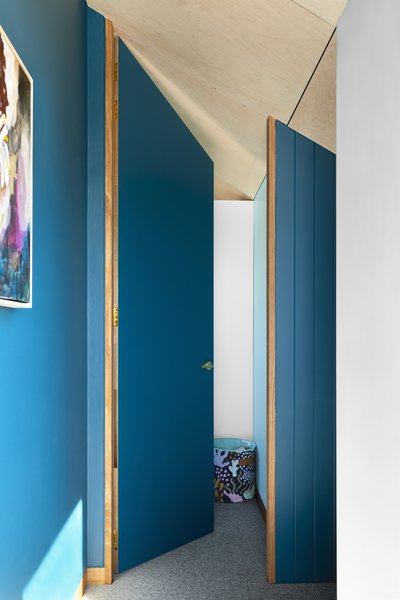 The door leading to one of the children's bedrooms on the upper level. The addition extends completely into the angled roof space to create a sense of volume.