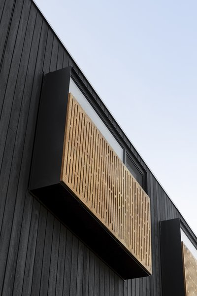 The extension is clad in charred black timber, which contrasts to the lighter, existing weatherboard structure. Graphic timber screens over the windows offer shading and privacy.