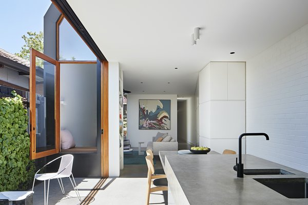 The angled joinery reflects light down the hallway and offers functional storage. It also naturally directs people from the living area toward the kitchen.