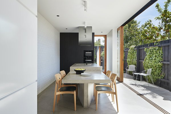 The kitchen/dining space is oriented sideways, making the most of the narrow site and opening out onto the rear courtyard to create an indoor/outdoor living space.
