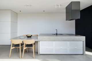The architect integrated a dining table into the kitchen island, embracing the common Australian practice of gathering informally in the kitchen.
