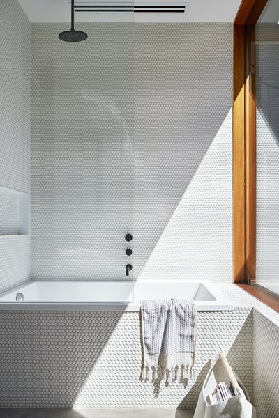 White penny tiles reflect natural light in the bathroom.