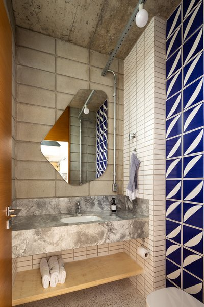 "The blue and white feature tiles in the bathroom were designed by renowned local architect Éolo Maia and were gifted to the couple by a friend. ""We were very happy because we admire Éolo Maia a lot,"" says Franchini. The bathroom counter is made from Bahia Calacatta marble."