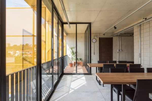 The yellow perforated metal screens warmly filter light into the commercial space.