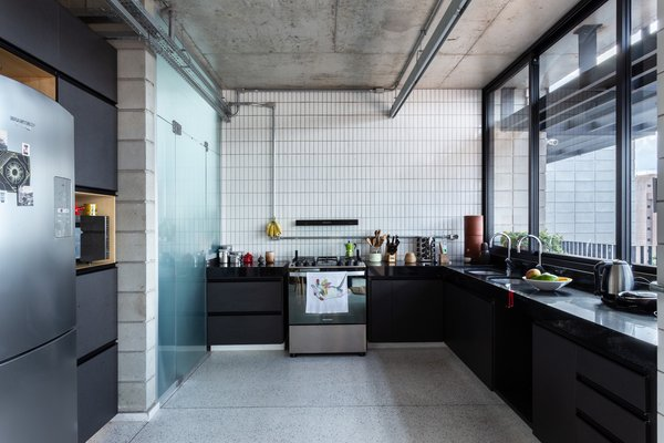 The kitchen features slightly industrial finishes—including concrete, glass and ceramic subway tiles—that are easy to clean and reflect natural light into the space.