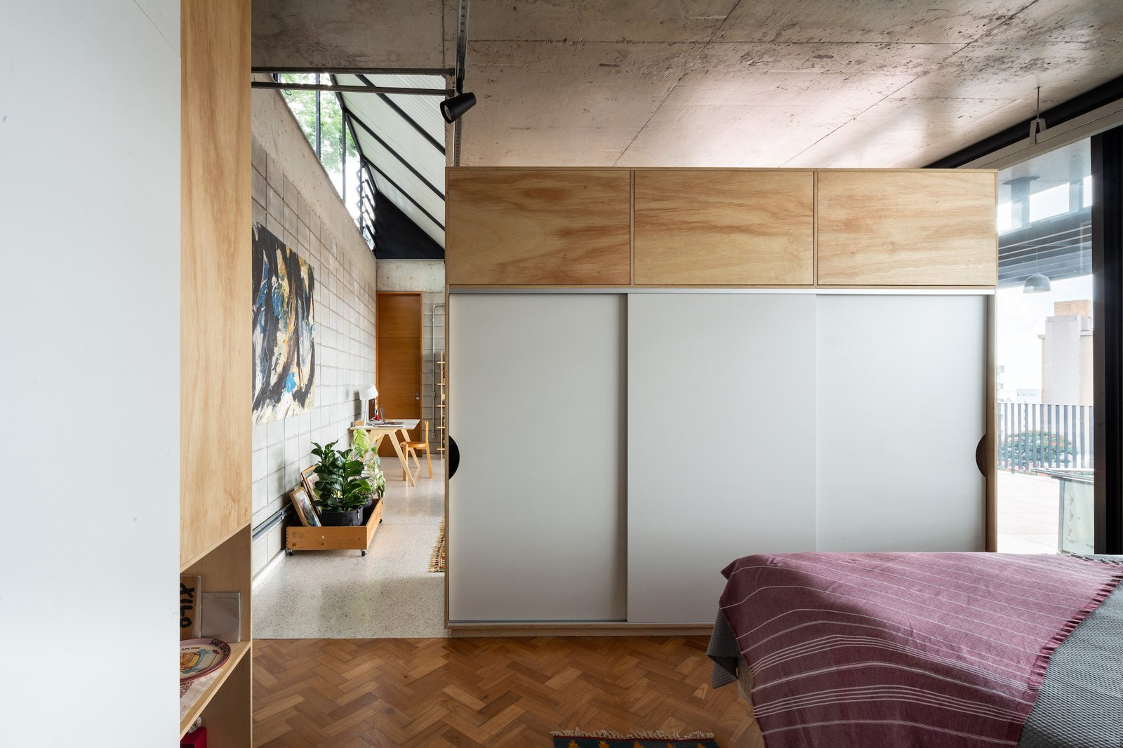 The view from the bedroom into the living space. The double-sided joinery unit features a wardrobe and storage space.
