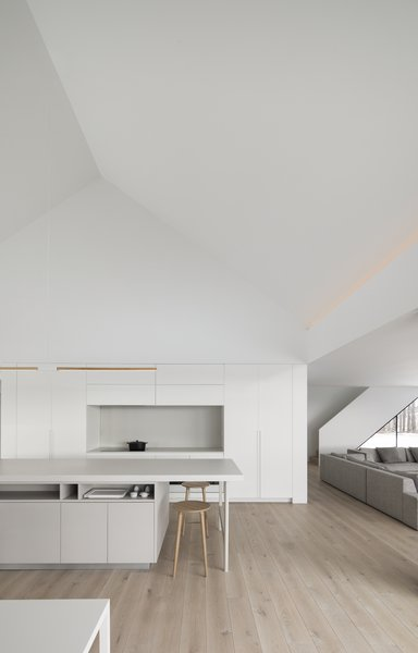 The all-white kitchen—as well as a bathroom and stair to the basement—forms a central core around which living spaces are arranged on the ground floor. The dramatic, double-height space echoes the form of the original building and makes the living space feel expansive and open.