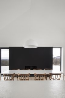 Painted steel panels frame the fireplace in the dining room and make the structure seemingly disappear, leaving only the fire visible. These steel panels also mirror the horizontal form and height of the kitchen wall it is facing.
