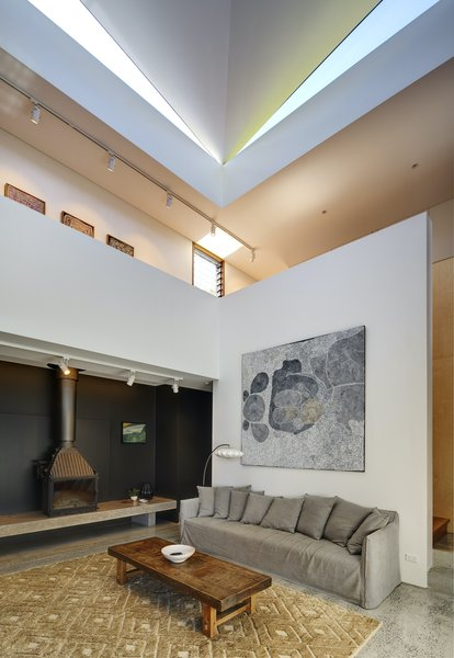 The living room features a Cheminee Philippe wood-burning fireplace, which has a large heating capacity. By placing it below the void, it is able to heat both the downstairs and common areas upstairs.