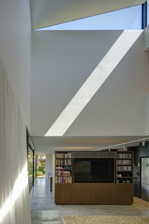 A bespoke timber joinery unit serves as a semi-partition between the kitchen and the living space, giving a sense of separation without disconnection. Dramatic patterns of light and shadow from the sculptural skylight play over the space.