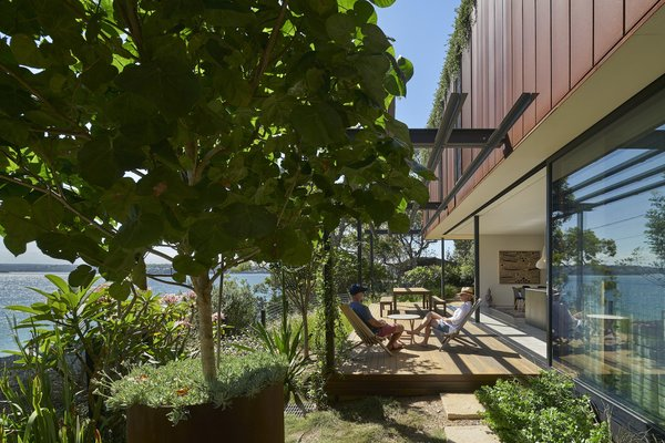 A fully glazed wall—which incorporates both louvres and sliding doors—connects the dining room and kitchen to the deck and garden. The natural slope of the site replaces the need for a fence between the garden and the beach.