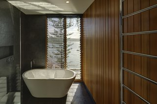 The bathrooms are dark-tiled with timber-lined walls to create a sense of intimacy and privacy.