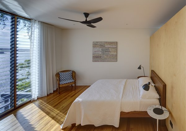"The master bedroom—located in the ""sleeping volume""—has views over the water. The bedrooms are left unheated, and ceiling fans are used for cooling in summer."