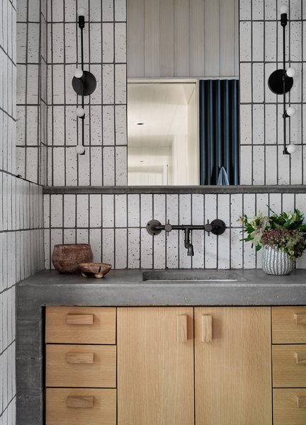The shared bathroom features warm, natural finishes, including concrete, timber, and ceramic tile.