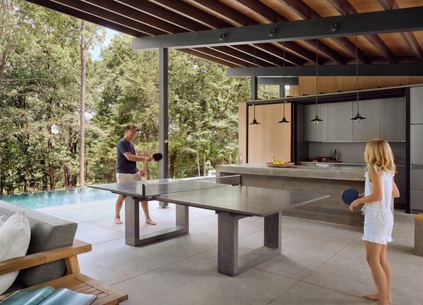 The outdoor dining table playfully converts to a ping pong table. The concrete kitchen island and dining table have been designed to be robust and low maintenance.