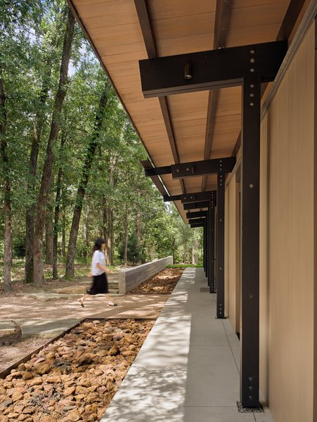 Materials are inspired by the region: the exterior pine siding references the color of nearby pine tree bark, and rip rap-filled basins highlight the iron ore found in East Texas.