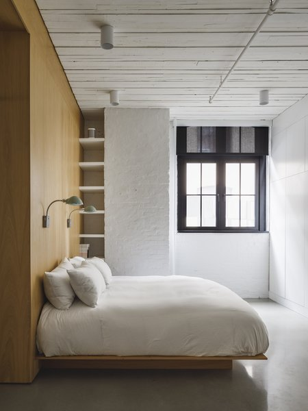 The reclaimed timber flooring was also used on the ceiling of the master bedroom, where it's painted white to brighten the space. The single window in the bedroom provides natural light for the private spaces.