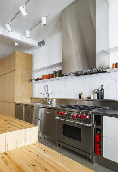 "The stainless steel kitchen features a Wolf 36"" gas cooktop and range hood. The client initially wanted to install a commercial-grade kitchen, but was unable to due to restrictions with the insurance and the condo association."