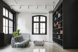 The apartment is accessed via an old freight elevator. The cabinetry around the elevator entrance—including a massive bookshelf and storage space—is black, contrasting with the white brick walls and the white oak joinery.