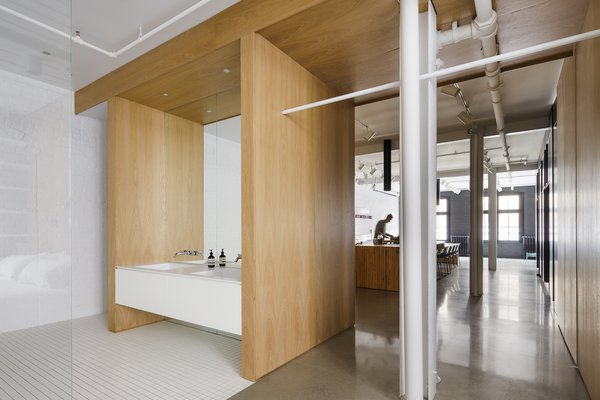 """White oak joinery divides the space and provides ample storage. It also allows the original sprinkler system and structure to be revealed and celebrated. """"We had to put up about 20 coats of special fire-retardant paint so that we could keep the steel structure visible,"""" says Béliveau."""