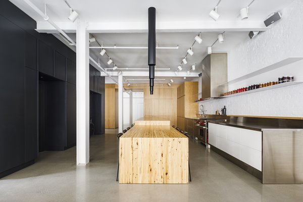 The elevator entrance opens to the kitchen and dining area, which is the social heart of the home. A line of statement halogen lights hang from the ceiling above the dining bench, which is clad in timber boards reclaimed from the original floor.