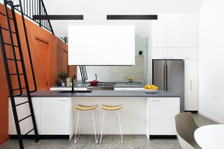 The kitchen features a mirrored backsplash that makes the space feel larger. The orange cabinetry conceals the laundry.