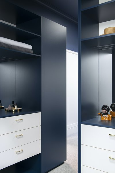 The walk-in wardrobe is painted the same midnight blue as the master bedroom.
