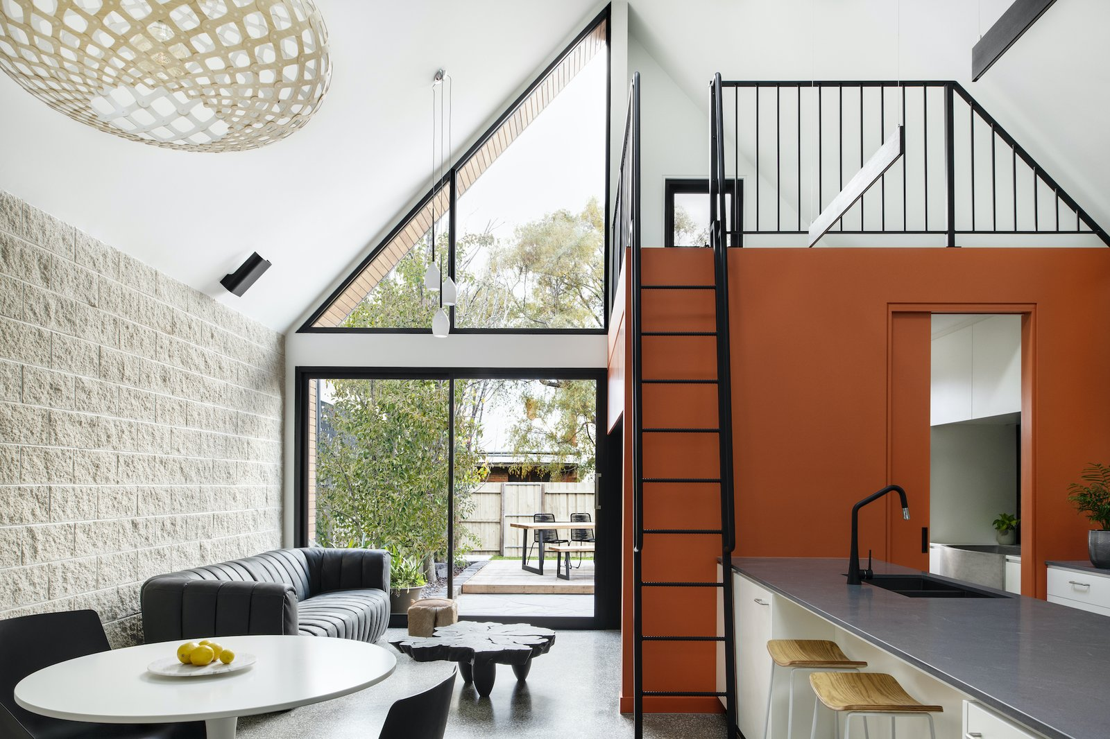 Living area and mezzanine at Cuckoo House by RARA Architecture.