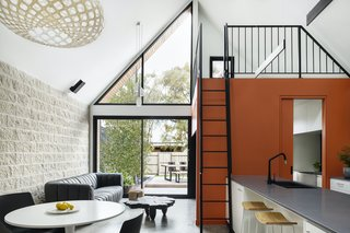 The mezzanine above the laundry will eventually be used as a study. The orange joinery beneath it functions as part of the entertainment unit and as storage for wine glasses.