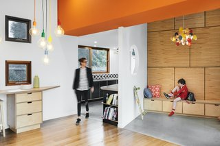 The angled entry foyer is wrapped in plywood with concealed access to roof storage spaces. Built-in seating provides storage for daily wares and a spot to put on shoes and drop school bags.